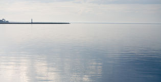 Faro en el mar con las ondas hermosas Imágenes de archivo libres de regalías