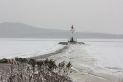 Faro en invierno en la playa imagen de archivo libre de regalías