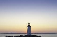 Faro en la ensenada de Peggy, Nueva Escocia en la puesta del sol Foto de archivo