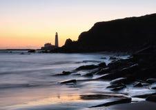 Faro en orilla en la puesta del sol Foto de archivo