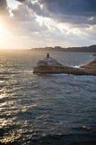 Faro en rocas sobre el mar Foto de archivo