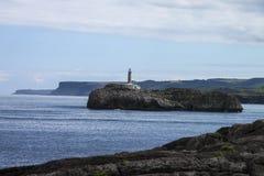 Faro en un acantilado de la costa escarpada fotografía de archivo