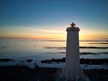 Faro islandés en la puesta del sol Imagenes de archivo