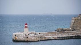 Faro ligero que destella en el embarcadero en el mar Nave en el fondo, agua, turismo, tormenta, naturaleza, paisaje marino almacen de metraje de vídeo