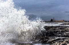 Faro nella tempesta. Stormy sea with waves on the rocks Stock Image
