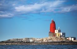 Faro norvegese con la grande torre rossa fotografia stock