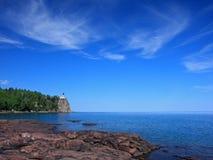 Faro partido de la roca en superior de lago Imagenes de archivo