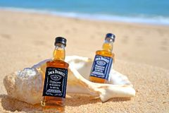 Faro, Portugal - 12/10/2018: Two little bottles Jack Daniels whiskey in the big ocean shell stand on the sand. Alcoholic party in stock photo