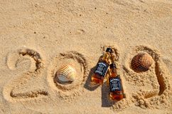 Faro, Portugal - 12/10/2018: Two little bottles Jack Daniels whiskey lie on the sand. New Year luxury alcoholic party, top view royalty free stock photo