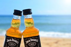 Faro, Portugal - 12/10/2018: Two little bottles Jack Daniels whiskey stand on the sand closeup. Alcoholic party in a nautical stock image