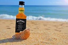 Faro, Portugal - 12/10/2018: weinig whisky van flessenjack daniels in oceaanshells bevindt zich op het zand Alcoholische partij i stock foto's