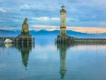 Faro que se coloca en un promontorio con una reflexión en el agua en la puesta del sol Imágenes de archivo libres de regalías