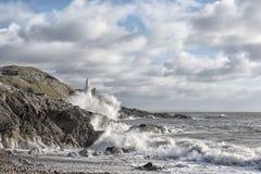 Faro rodeado por las ondas en un día nublado Fotos de archivo libres de regalías
