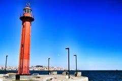 Faro rojo en el puerto de pueblo de Almada en Lisboa imagen de archivo