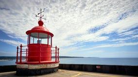 Faro rojo en fondo del cielo azul y del mar imagenes de archivo
