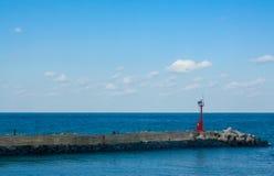 Faro rojo por el mar imagen de archivo