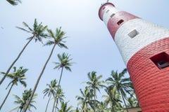 Faro rojo y blanco rodeado por las palmeras en la India Imágenes de archivo libres de regalías