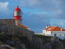 Faro rosso su Cabo de Sao Vicente con la parete di pietra fotografia stock