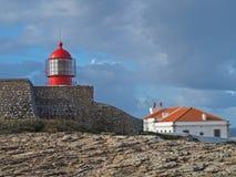 Faro rosso su Cabo de Sao Vicente con la parete di pietra fotografie stock