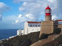 Faro rosso su Cabo de Sao Vicente con la parete di pietra immagine stock