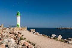 Faro su un capo marino all'entrata del porto Immagini Stock