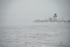 Faro su una penisola nella nebbia fredda fotografia stock