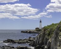 Faro su una riva rocciosa fotografia stock
