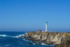 Faro su una scogliera sull'oceano con le onde un bello giorno di estate fotografia stock