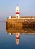 Faro viejo con la reflexión de la agua de mar Imagen de archivo libre de regalías