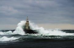 Faro viejo en el mar en día tempestuoso Imagen de archivo libre de regalías