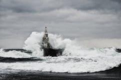 Faro viejo en el mar en día tempestuoso Fotos de archivo