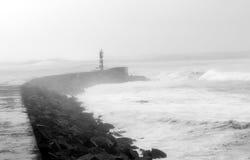 Faro visto de una playa Fotos de archivo libres de regalías