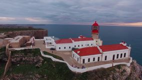 Faro y acantilados de la visión aérea en el cabo St Vincent en la puesta del sol Sagres, Algarve, Portugal almacen de metraje de vídeo