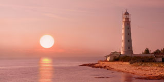 Faro y puesta del sol imagenes de archivo