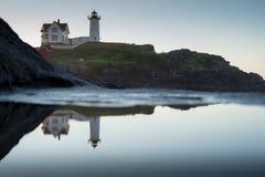 Faro y reflexión de la protuberancia pequeña después del amanecer Imagen de archivo