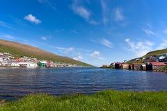 Faroe Island liten by som förbiser en fjord Royaltyfri Foto
