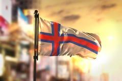 Faroe Islands Flag Against City Blurred Background At Sunrise Ba. Cklight Sky Royalty Free Stock Photos