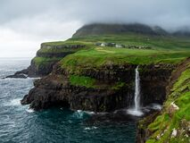 Faroe Islands. Múlafossur Waterfall and Gasadalur village over the the waterfall. Long exposure.