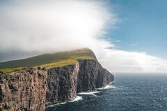 Faroe Islands Traelanipa the slaves rock cliff is seen rising over the ocean next to lake Sorvagsvatn. Clouds and blue
