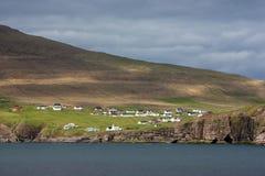Faroe Islands, village of Viðareiði. Faroe, a view of Viðareiði with its rocky sea cliffs under a dark sky royalty free stock photos