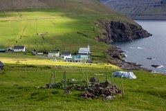 Faroe Islands, village of Viðareiði. Faroe, a view of Viðareiði . A village in the midst of green fields and rocky sea cliffs . Some rays of sunlight stock photography