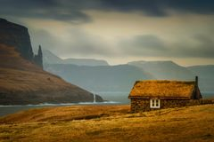 Faroese grassy cabin. Lonely old cabin with grassy roof and Witch`s Finger rock in background, Faroe Islands stock photo