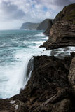 Faroese Waterfall. Lake emptying into the sea - Midavagur - Faroe Islands Stock Photos