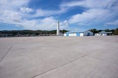 Farol contra o céu azul com as nuvens brancas no porto da boa Imagens de Stock