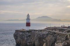 Farol de Gibraltar no penhasco pelo mar com montanhas dentro distante Imagem de Stock Royalty Free