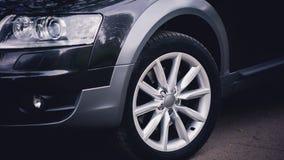 Farol de um carro preto moderno As rodas dianteiras do carro Detalhes modernos do exterior do carro fotografia de stock