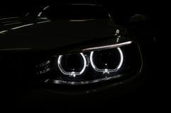 Farol do carro com o luminoso no preto Foto de Stock Royalty Free