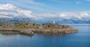 Farol em um cabo rochoso em um fundo das montanhas, Lofoten, Noruega Imagem de Stock Royalty Free