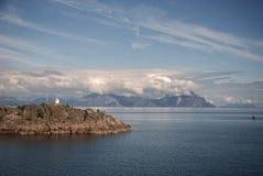 Farol em um cabo rochoso em um fundo das montanhas, Lofoten, Noruega Fotografia de Stock