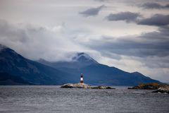 Farol Les Eclaireurs, en röd och vit gjord randig fyr på den steniga ön på beaglekanalen, Ushiaia, Argentina royaltyfri fotografi